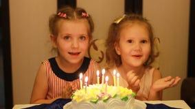 Meisjeszuster op een kind` s verjaardag De kinderen maken een wens en slag kaarsen op de cake op stock videobeelden