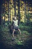 Meisjezitting alleen op een Rots in Bos stock afbeeldingen