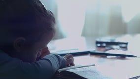 Meisjezitting bij de lijsttekening in een kleurend boek vroeg in de ochtend stock footage