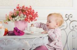 Meisjezitting bij een lijst met thee en decoratie, portrai Stock Foto