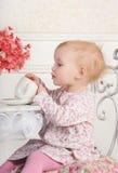 Meisjezitting bij een lijst met thee en decoratie, portrai Stock Fotografie