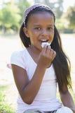 Meisjezitting bij gras het eten Stock Foto's
