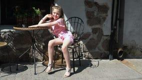 Meisjezitting buiten bij lijst die in de heldere zon inekrimpen stock footage