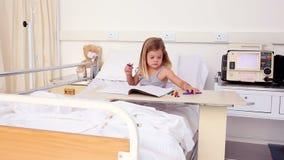 Meisjezitting in de kleuring van het het ziekenhuisbed stock video
