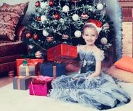 Meisjezitting dichtbij Kerstboom met een grote gift Royalty-vrije Stock Foto's