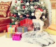 Meisjezitting dichtbij Kerstboom met een grote gift Stock Fotografie
