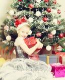 Meisjezitting dichtbij Kerstboom met een grote gift Stock Foto