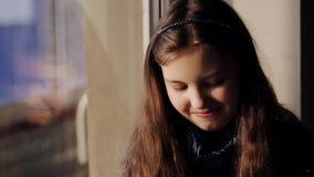 Meisjezitting door het venster en het glimlachen stock video