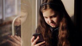 Meisjezitting door het venster met een telefoon in zijn hand stock footage