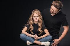 Meisjezitting en vader die haar koesteren op zwarte stock fotografie