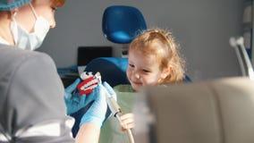 Meisjezitting in het tandstoel spelen met tandhulpmiddelen en speelgoed, voorbereiding voor tanden het schoonmaken stock videobeelden