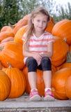 Meisjezitting met grote pompoenen Stock Fotografie