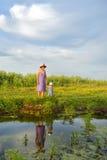 Meisjezitting met haar moeder dichtbij het meer en hun bezinningen stock fotografie