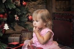 Meisjezitting onder de Kerstboom Stock Foto's