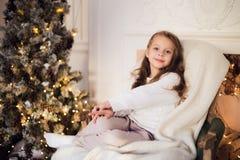 Meisjezitting op comfortabel thuis verpakt in een algemene ochtend van de stoelkerstboom Royalty-vrije Stock Afbeelding