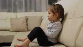 Meisjezitting op de bank en het letten op TV stock video