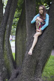 Meisjezitting op de takken van de boom Royalty-vrije Stock Foto
