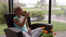 Meisjezitting op de zonzitkamer tijdens de regen met kop van hete drank stock footage