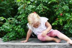 Meisjezitting op een bank in de tuin royalty-vrije stock afbeelding