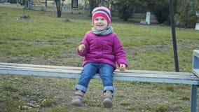 Meisjezitting op een bank in het park en het bengelen van haar voeten stock footage
