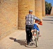 Meisjezitting op een fiets van haar grootvader stock foto