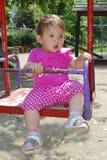 Meisjezitting op een schommeling op de speelplaats Stock Fotografie