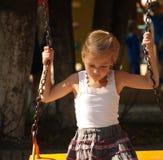 Meisjezitting op een schommeling in een stadspark op een de zomermiddag stock fotografie