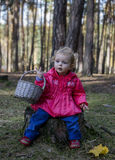 Meisjezitting op een stomp in het hout met een mand Stock Foto
