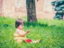 Meisjezitting op gras die zijn hand bekijken Royalty-vrije Stock Afbeeldingen