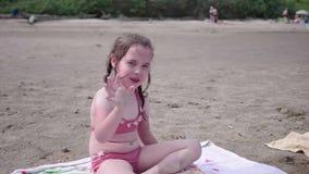 Meisjezitting op het strand, hete de zomerdag Het golven en het glimlachen stock footage