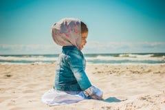 Meisjezitting op het zand bij het strand Royalty-vrije Stock Foto