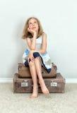 Meisjezitting op koffers stock fotografie