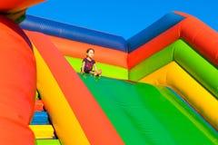 Meisjezitting op opblaasbare trampoline Stock Foto's
