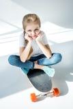Meisjezitting op skateboard met gekruiste benen royalty-vrije stock fotografie