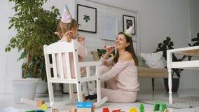 Meisjezitting in schommelstoel en spel met moeder stock footage