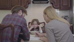 Meisjezitting voor droevig en ongelukkige ouders, eet zij niet Jonge vrouw en man zitting bij de lijst stock videobeelden