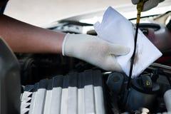 Meister, Abwischen der Ölmessstab, zum des Öls im Auto mit einem weißen Lappen zu überprüfen Lizenzfreie Stockfotografie