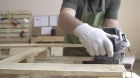 Meister in den weißen Handschuhen und in einem grünen Schutzblech arbeitet mit Werkzeugen für das Reiben Auf dem Hintergrund des  stock footage