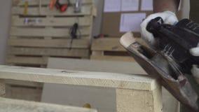 Meister in den weißen Handschuhen und in einem grünen Schutzblech arbeitet mit Werkzeugen für das Reiben Hölzerne Sachen für das  stock video footage