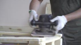 Meister in den weißen Handschuhen und in einem grünen Schutzblech behandelt einen Holzbalken Nahaufnahme beim Arbeiten mit Naturh stock footage