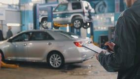 Meister in der Autowerkstatt, die Auto in einer Garage überprüfend tut Stockfotografie