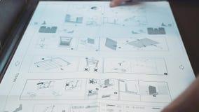 Meister, der Möbel produziert und installiert, zeigt eine Zeichnung auf dem Tisch an Nahaufnahme stock video footage