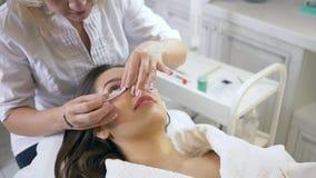 Meister des Schönheitssalons setzt Flecken unter Augen des weiblichen Patienten, Beginn des Verfahrens für Wimpererweiterung stock video footage