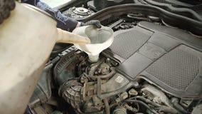 Meister durch den Trichter beginnt, Motorenöl in einem Automotor zu gießen stock video