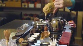 Meister gießt Teeblätter mit Wasser Grüner Tee mit Cup und Teekanne stock footage