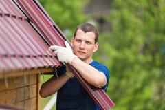 Meister hält seine Hände auf einer Trompete auf dem Hintergrund eines Dachs stockfotos