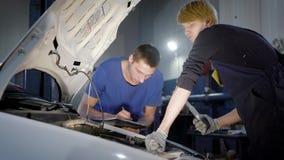 Meister kontrolliert innere Systeme des Automobils in einem Fahrzeugkarosserieshop, Assistent schreibt Ergebnisse auf ein Papierb stock video footage