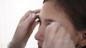 Meister korrigiert Augenbrauen in einem Schönheitssalon und misst die perfekte Form für Kundengesicht Berufssorgfalt für Gesicht  stock video