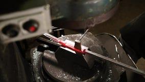 Meister macht Form für Metalldetail auf einer hydraulischen Hammermaschine in der Schmiede stock footage
