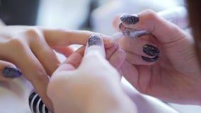 Meister macht Hardware-Maniküre Manikürist wendet elektrisches Nagelfeilebohrgerät an der Maniküre auf weiblichen Fingern an stock footage